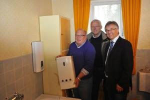 Uralt gegen Neu: Wilhelm Kleinesdar (links), Installateur Ulrich Dresing und Stiebel-Eltron-Mitarbeiter Gerhard Langner (rechts) verabschieden den Durchlauferhitzer DH 18 in den verdienten Ruhestand. Der neue DEL hängt bereits an der Wand.